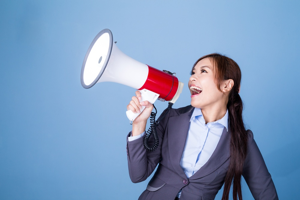Businesswoman making announcement with megaphone