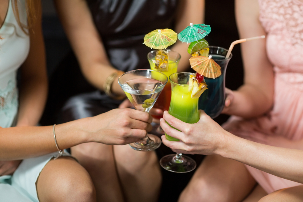 Mid section of female friends toasting glasses of cocktail in bar