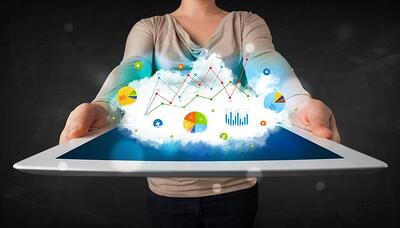 Person holding a white touchpad with cloud technology and charts.jpeg