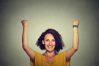 Successful woman with arms up celebrating